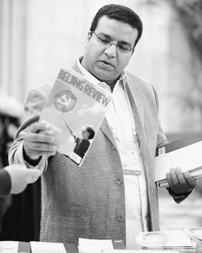 一名本国记者正在十八大新闻中心报纸杂志区选择感兴趣的书刊。群众视觉