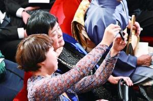 12月10日,莫言的夫人杜勤兰(上)、女儿管笑笑在颁奖现场拍照。 新华网发